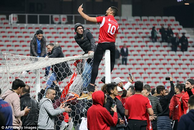 Tunisia fans invade pitch, set off flares and climb goalposts in wild celebrations